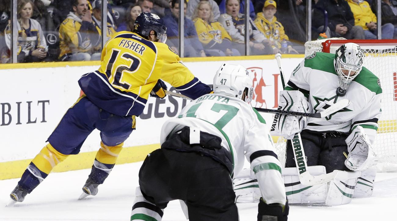 Dallas Stars goalie Antti Niemi, of Finland, holds the puck in place with his mask as Nashville Predators forward Mike Fisher (12) reaches for a possible rebound in the second period of an NHL hockey game Monday, Feb. 15, 2016, in Nashville, Tenn. (AP Pho