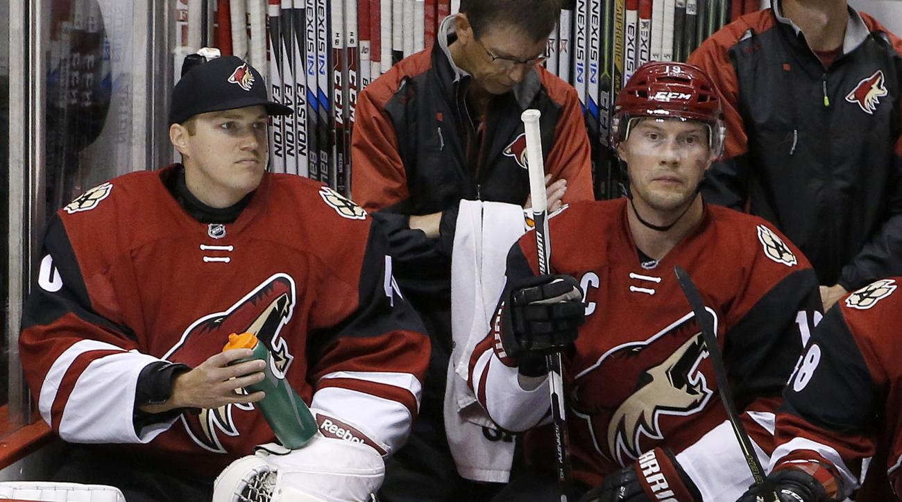 Arizona Coyotes backup goalie Nathan Schoenfeld, left, signed to the team only hours prior to the game due to an injury to goalie Anders Lindback, sits next to Shane Doan during the second period of an NHL hockey game Monday, Feb. 15, 2016, in Glendale, A
