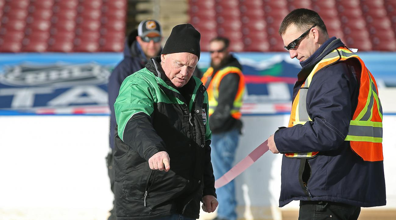 National Hockey League's Dan Craig, left, and Minnesota Wild's Travis Larson, right, help on transforming TCF Bank Stadium into a world-class hockey venue, Tuesday, Feb. 16, 2016 in Minneapolis, for the upcoming 2016 NHL Stadium Series that will be taking