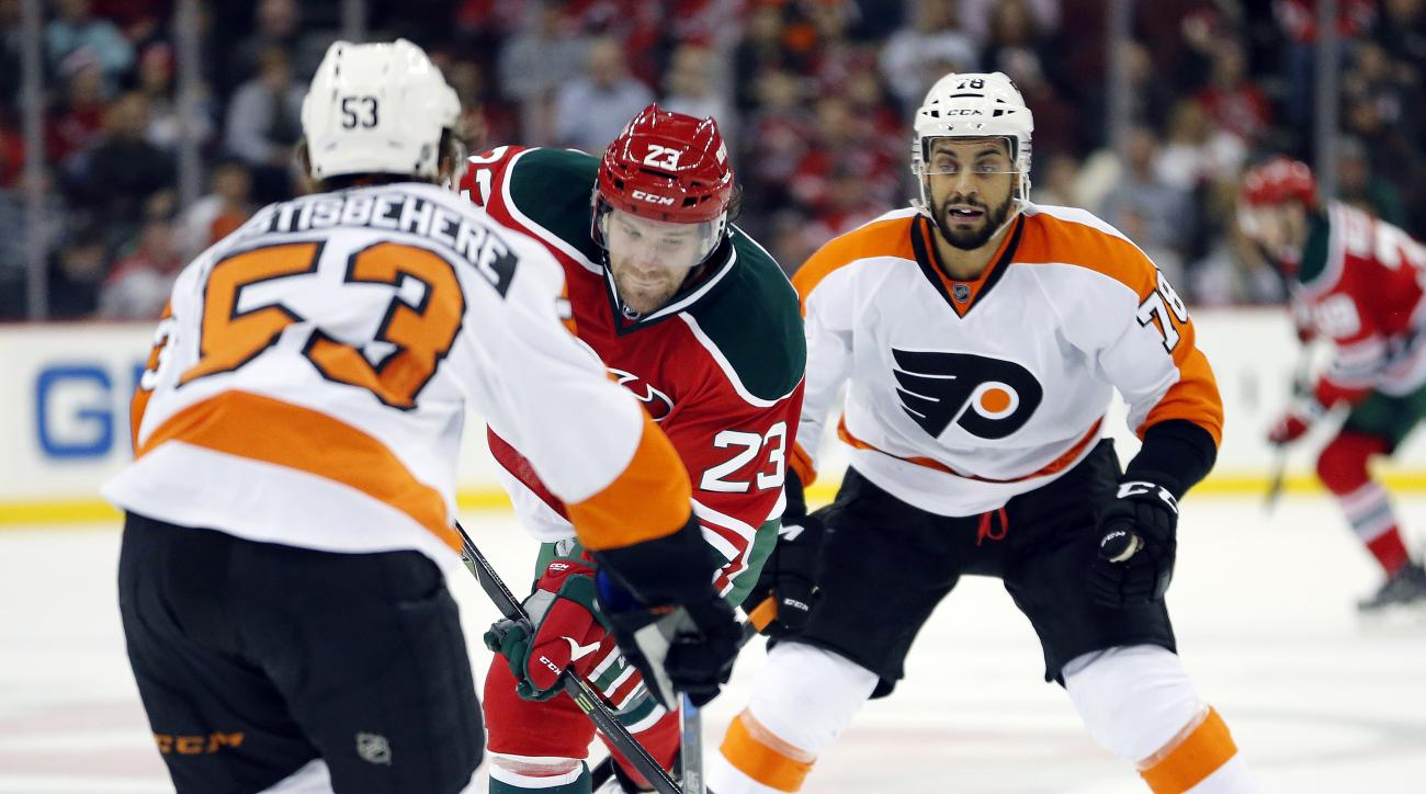New Jersey Devils right wing Bobby Farnham, center, shoots as Philadelphia Flyers defenseman Shayne Gostisbehere (53) and right wing Pierre-Edouard Bellemare (78), of France, defend during the second period of an NHL hockey game, Tuesday, Feb. 16, 2016, i