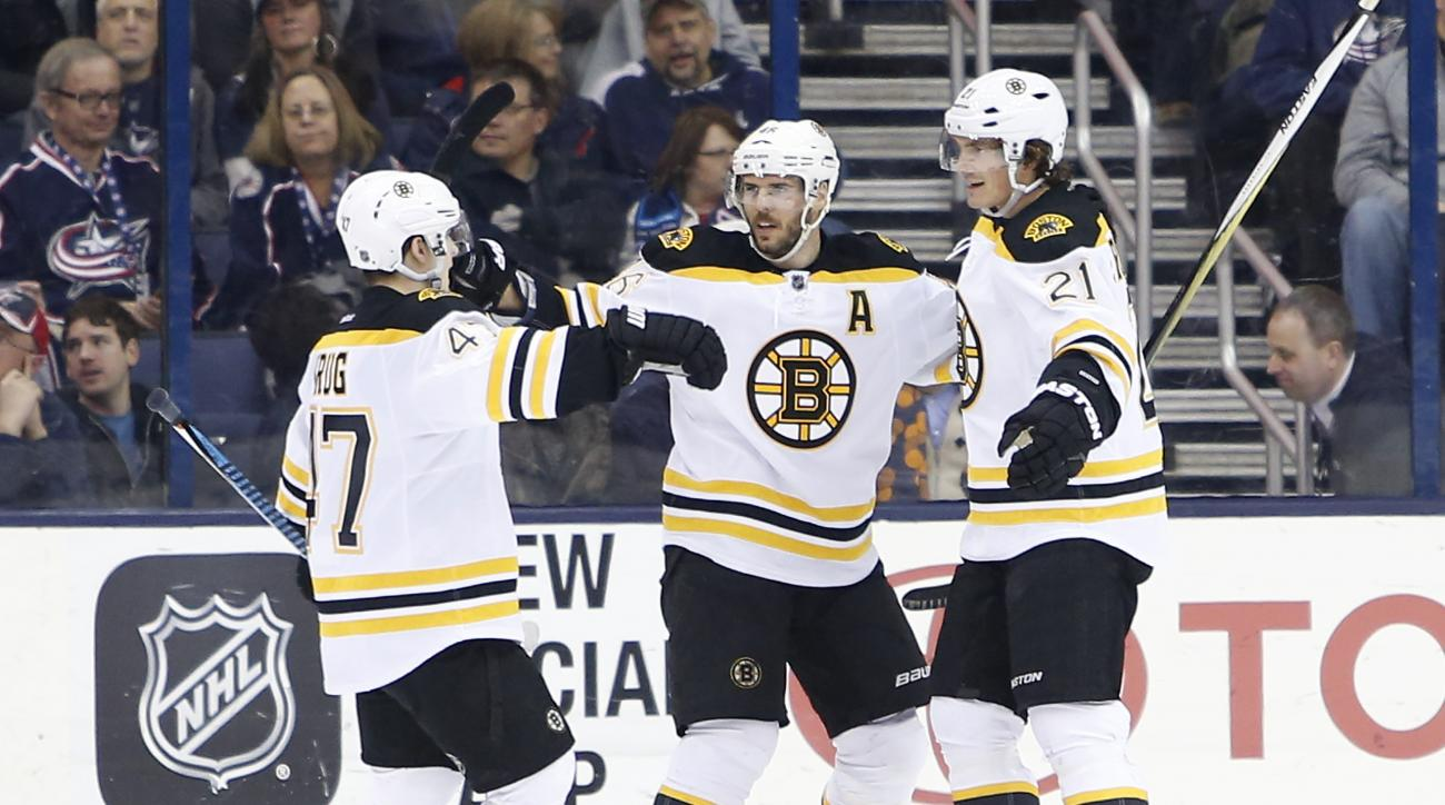 Boston Bruins' Loui Eriksson, right, of Sweden, celebrates his game-winning goal against the Columbus Blue Jackets with teammates Torey Krug, left, and David Krejci, of the Czech Republic, during the overtime period of an NHL hockey game Tuesday, Feb. 16,
