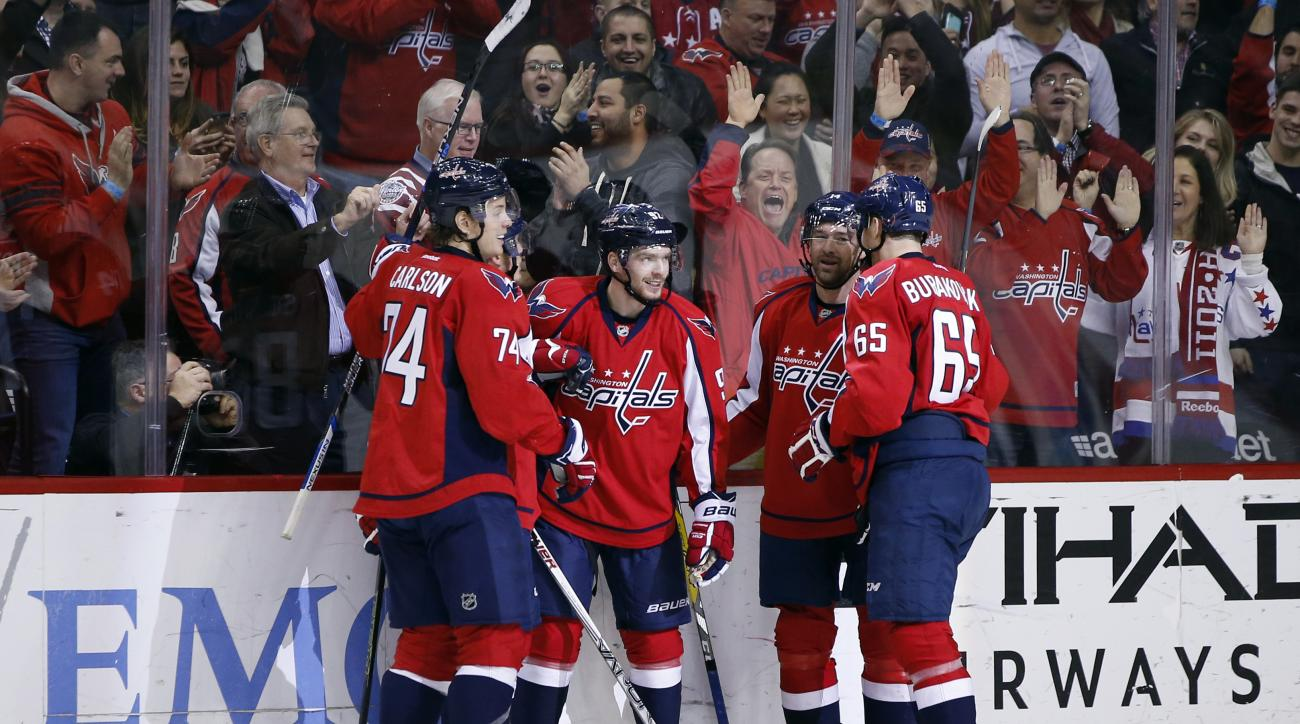Washington Capitals center Evgeny Kuznetsov, center, from Russia, celebrates his go ahead goal with his teammates in the third period of an NHL hockey game against the Los Angeles Kings, Tuesday, Feb. 16, 2016, in Washington. The Capitals won 3-1. (AP Pho