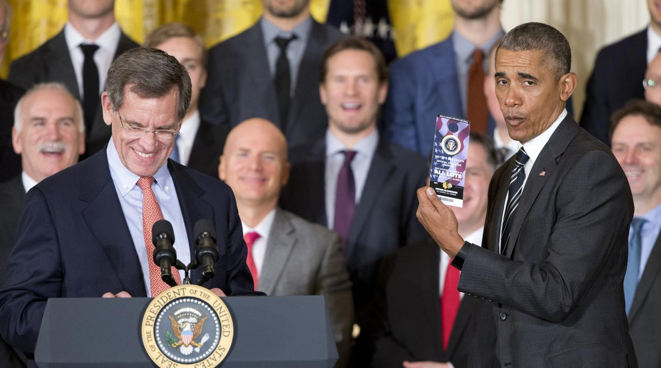 President Barack Obama, right, holds up a parking pass that was presented to him by Rocky Wirtz, left,  Chairman of the team, during a ceremony to honor the 2015 NHL Stanley Cup Champion Chicago Blackhawks in the East Room of the White House in Washington