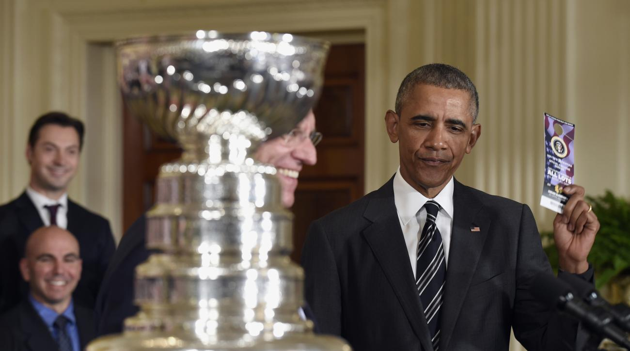 President Barack Obama holds up a hangtag parking pass that he was given to him by Chicago Blackhawks hockey team Chairman Rocky Wirtz, left, Thursday, Feb. 18, 2016, during a ceremony to honor the 2015 NHL Stanley Cup Champion Chicago Blackhawks in the E