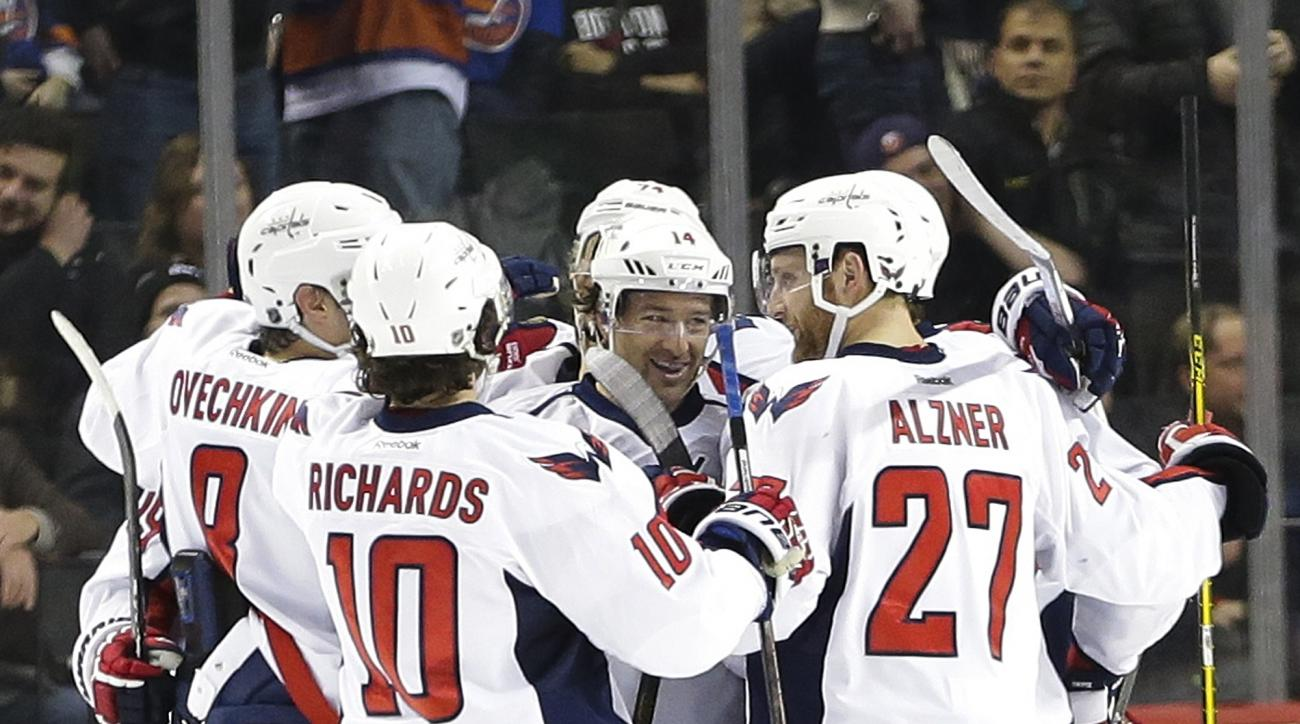 Washington Capitals' Justin Williams, center, celebrates with teammates after scoring the game winning goal during the overtime period of an NHL hockey game against the New York Islanders Thursday, Feb. 18, 2016, in New York. The Capitals won 3-2. (AP Pho