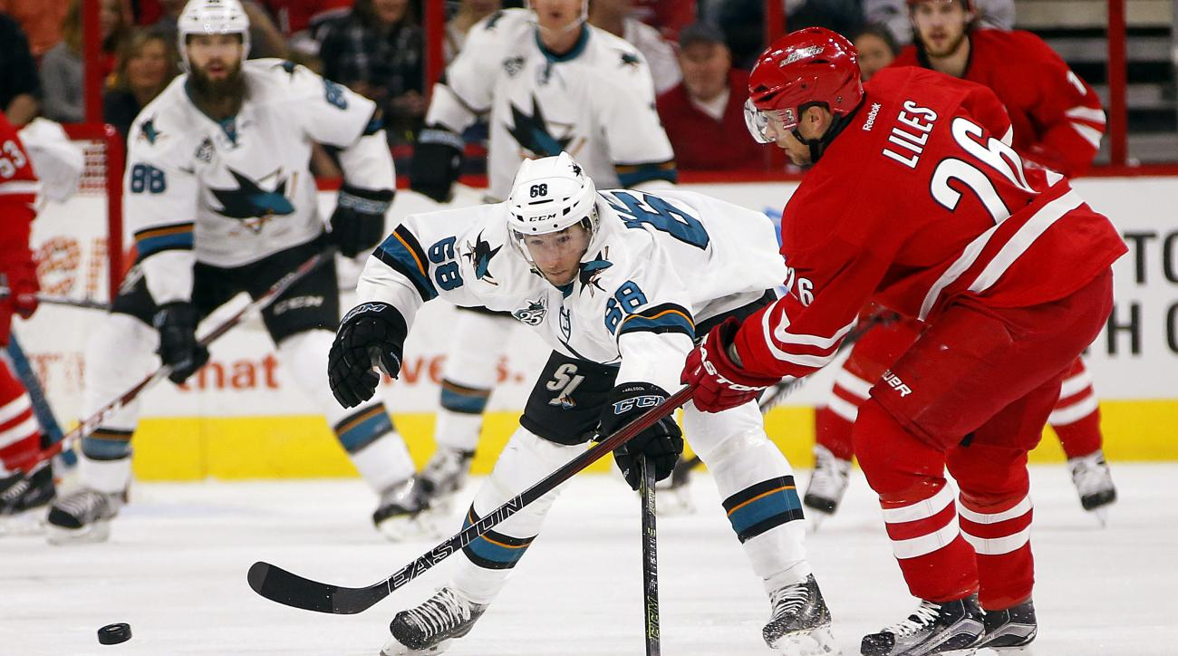 Carolina Hurricanes' John-Michael Liles (26) passes the puck by San Jose Sharks' Melker Karlsson (68) of Sweden, during the first period of an NHL hockey game Friday, Feb. 19, 2016, in Raleigh, N.C. (AP Photo/Karl B DeBlaker)