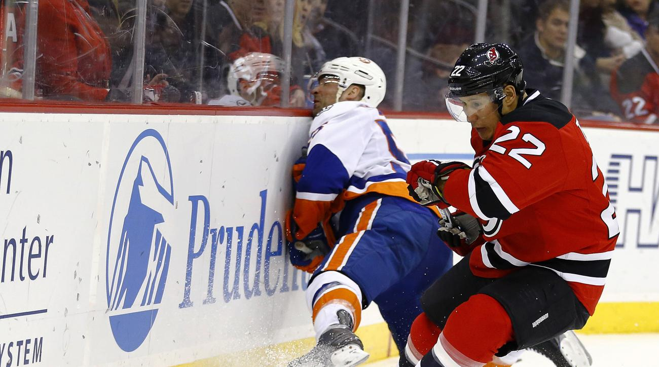 New York Islanders defenseman Johnny Boychuk, left, slams onto the boards as New Jersey Devils right wing Jordin Tootoo defends during the second period of an NHL hockey game, Friday, Feb. 19, 2016, in Newark, N.J. (AP Photo/Julio Cortez)