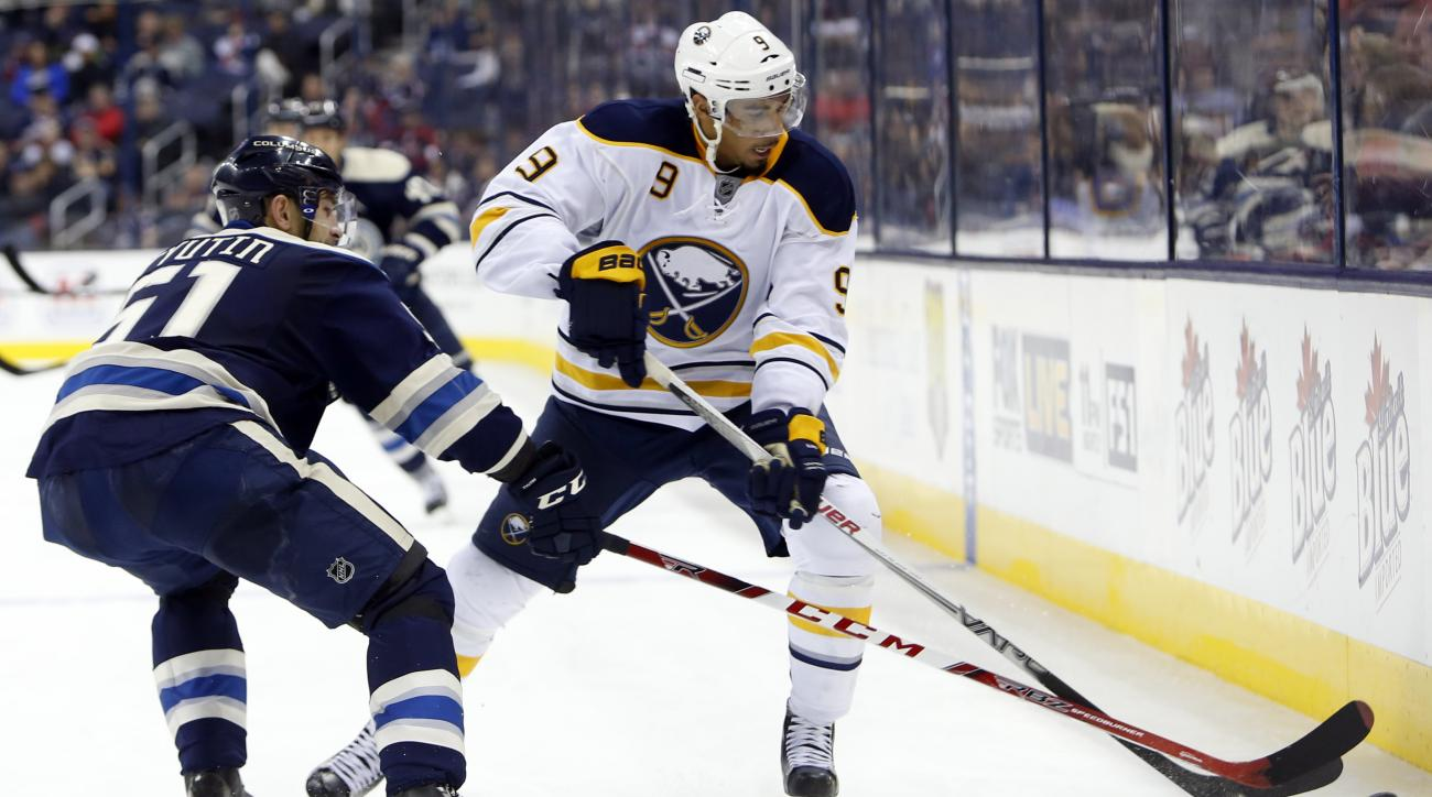 Buffalo Sabres' Evander Kane, right, carries the puck upice as Columbus Blue Jackets' Fedor Tyutin, of Russia, defends during the third period of an NHL hockey game Friday, Feb. 19, 2016, in Columbus, Ohio. The Sabres won 4-0. (AP Photo/Jay LaPrete)