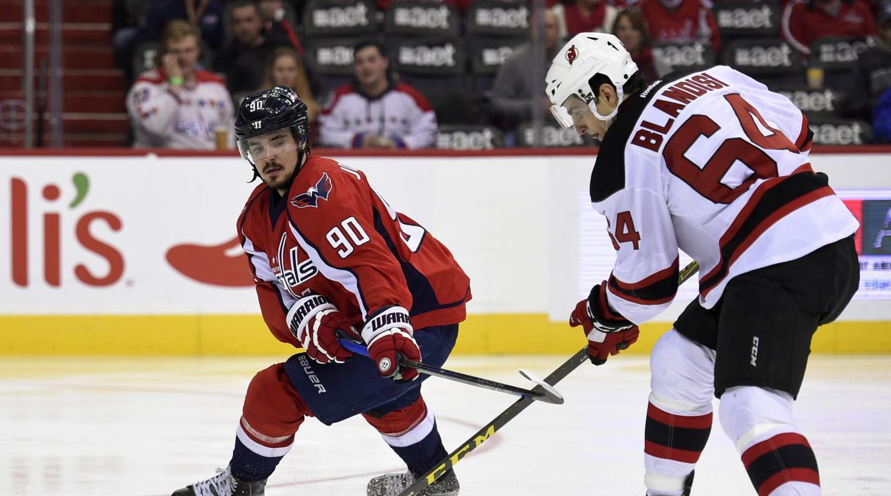 Washington Capitals center Marcus Johansson (90), of Sweden, reaches for the puck against New Jersey Devils center Joseph Blandisi (64) during the second period of an NHL hockey game, Saturday, Feb. 20, 2016, in Washington. (AP Photo/Nick Wass)