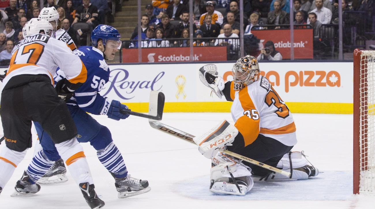 Toronto Maple Leafs' center Byron Froese (56) applies pressure to the net as Philadelphia Flyers' goalie Steve Mason watches the puck bounce off the post during second-period NHL hockey game action in Toronto, Saturday, Feb. 20, 2016. (Chris Young/The Can