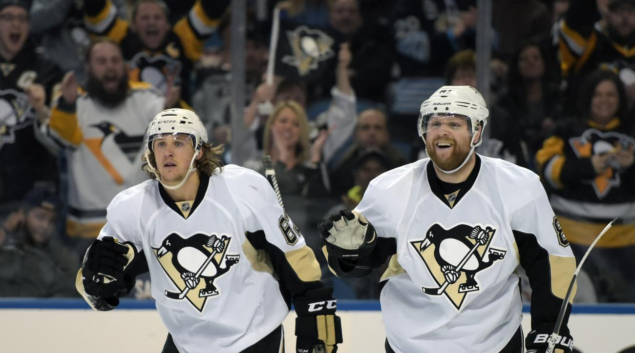 Pittsburgh Penguins' Carl Hagelin, left, of Sweden, celebrates with teammate Phil Kessel, right, after a goal by Kessel during the second period of an NHL hockey game Sunday, Feb. 21,  2016, in Buffalo, N.Y. (AP Photo/Gary Wiepert)