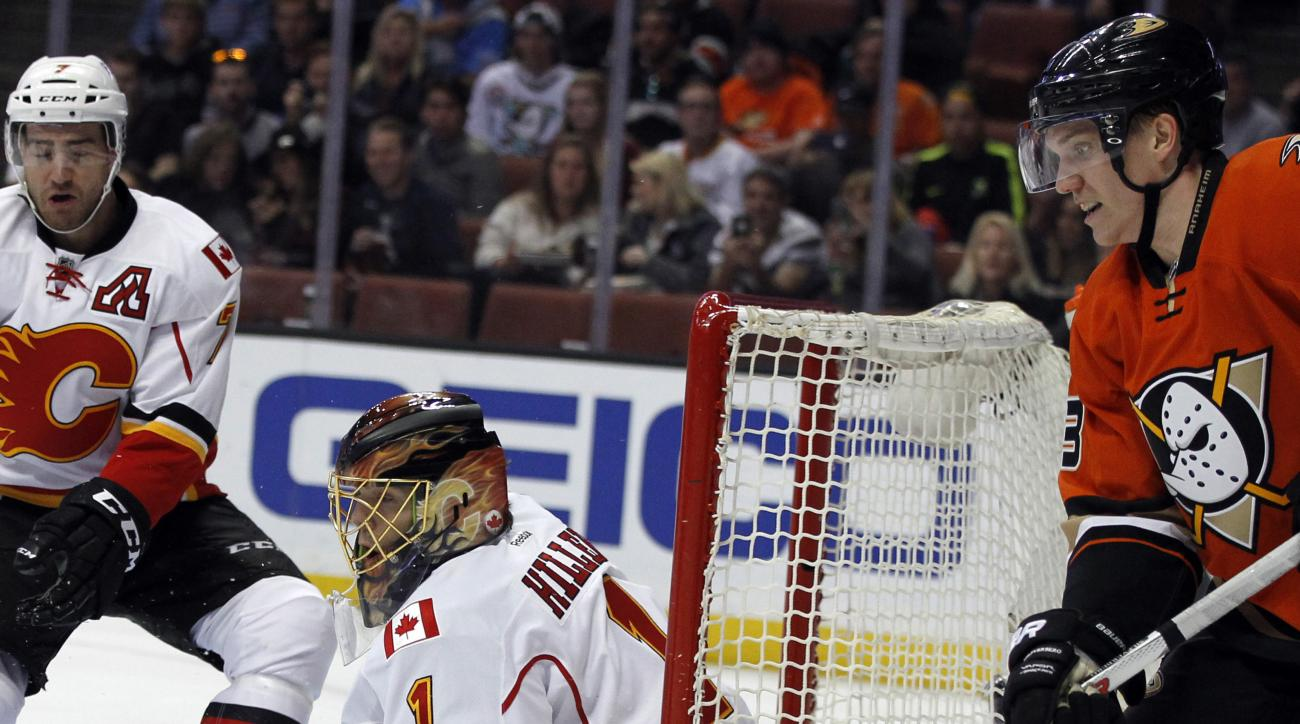 Anaheim Ducks left wing Jakob Silfverberg (33), of Sweden, shots gets blocked by Calgary Flames goalie Jonas Hiller (1), of Switzerland, with defenseman T.J. Brodie, left, looking on during the second period of an NHL hockey game in Anaheim, Calif., Sunda