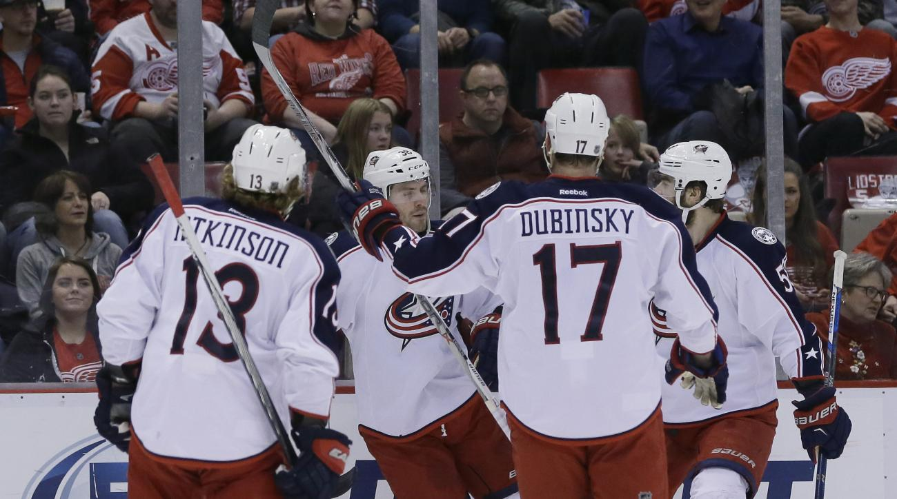 Columbus Blue Jackets center Boone Jenner, center, is congratulated by teammates after his goal during the first period of an NHL hockey game against the Detroit Red Wings, Tuesday, Feb. 23, 2016, in Detroit. (AP Photo/Carlos Osorio)