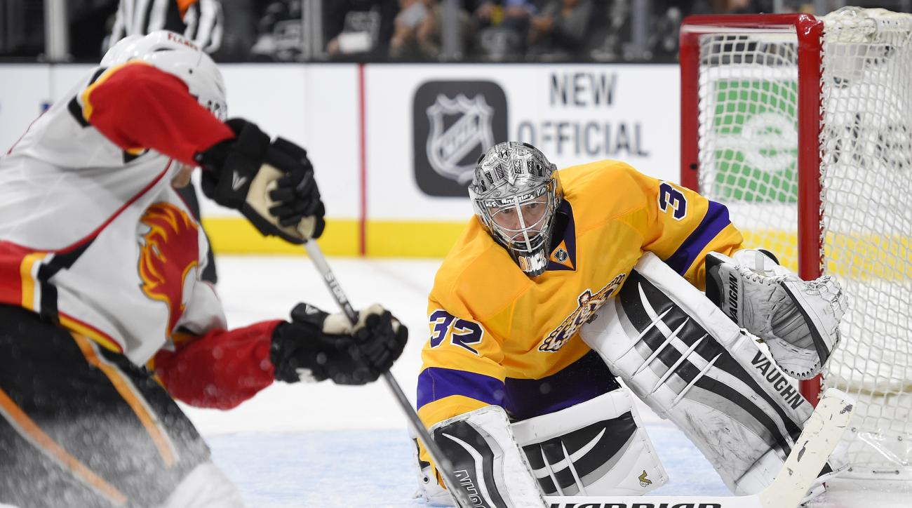 Calgary Flames center Sam Bennett, left, tries to get a shot in on Los Angeles Kings goalie Jonathan Quick during the third period of an NHL hockey game, Tuesday, Feb. 23, 2016, in Los Angeles. The Kings won 2-1. (AP Photo/Mark J. Terrill)