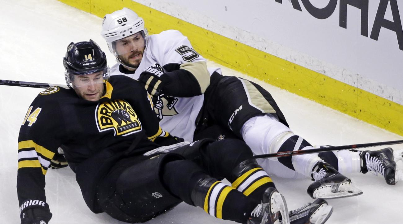Boston Bruins right wing Brett Connolly (14) and Pittsburgh Penguins defenseman Kris Letang (58) slide as they compete for the puck in the first period of an NHL hockey game, Wednesday, Feb. 24, 2016, in Boston. (AP Photo/Elise Amendola)