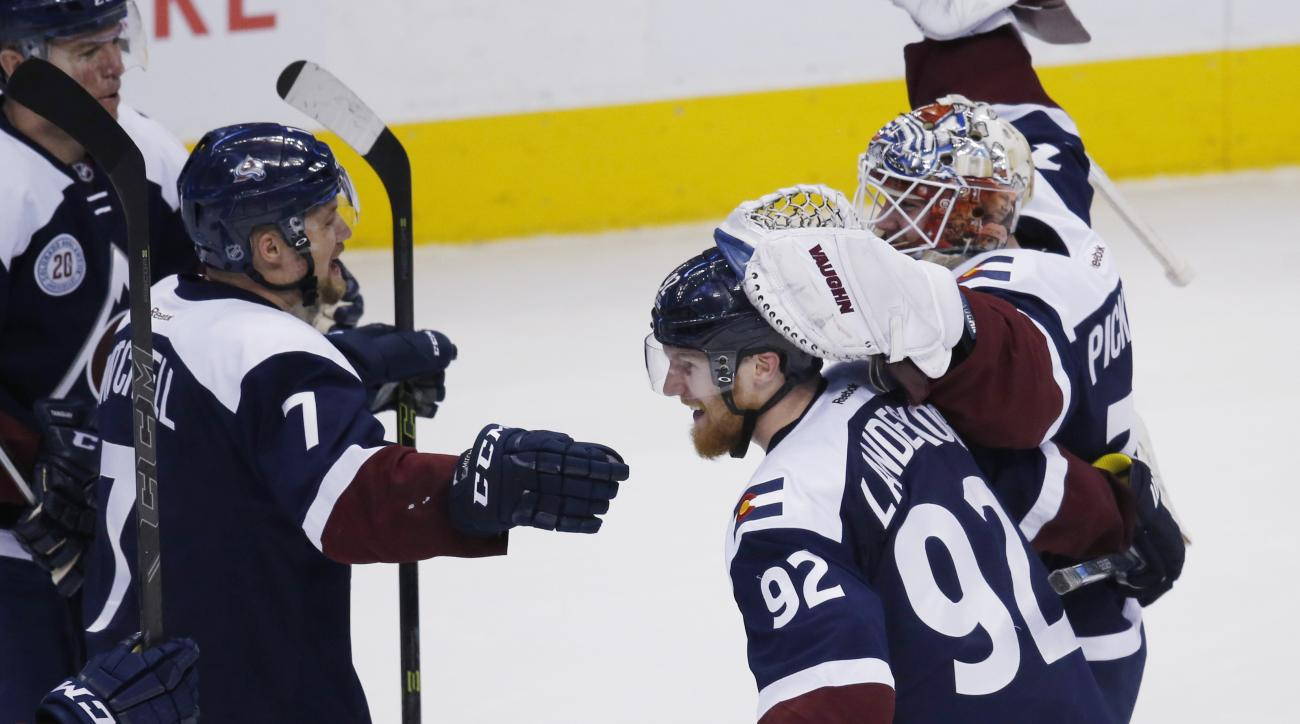 Colorado Avalanche center John Mitchell, left, celebrates with left wing Gabriel Landeskog, front right, of Sweden, and goalie Calvin Pickard after an NHL hockey game against the San Jose Sharks on Wednesday, Feb. 24, 2016, in Denver. The Avalanche won 4-