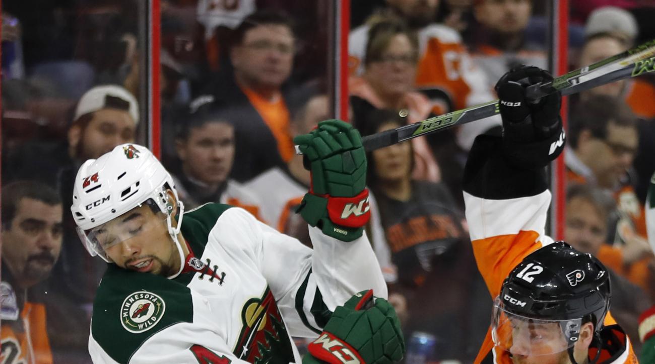 Minnesota Wild's Matt Dumba, left, and Philadelphia Flyers' Michael Raffl collide during the second period of an NHL hockey game, Thursday, Feb. 25, 2016, in Philadelphia. (AP Photo/Matt Slocum)