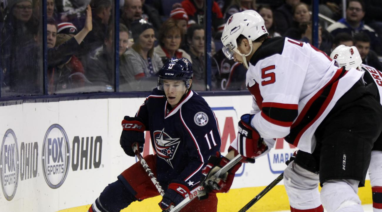 Columbus Blue Jackets' Matt Calvert, left, works for the puck against New Jersey Devils' Adam Larsson, of Sweden, during the second period of an NHL hockey game in Columbus, Ohio, Thursday, Feb. 25, 2016. (AP Photo/Paul Vernon)
