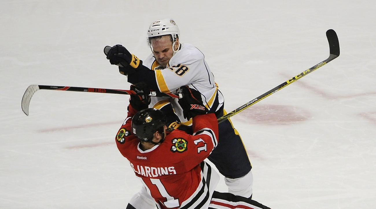 Nashville Predators center Paul Gaustad (28) checks Chicago Blackhawks center Andrew Desjardins (11) duiring the second period of an NHL hockey game Thursday, Feb. 25, 2016, in Chicago. (AP Photo/David Banks)