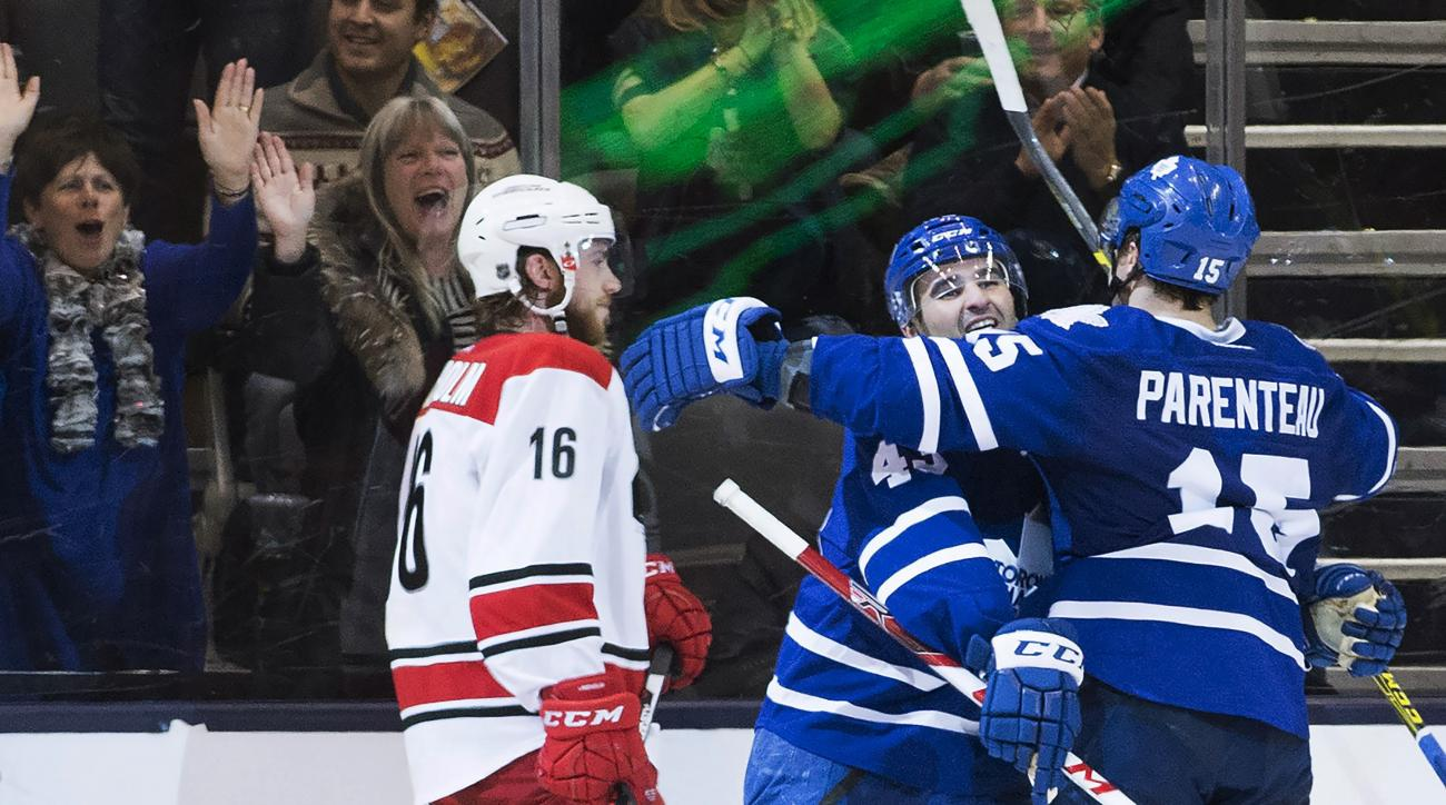 Toronto Maple Leafs right wing P.A. Parenteau (15) celebrates his goal with Maple Leafs center Nazem Kadri (43) as Carolina Hurricanes center Elias Lindholm (16) skates by during the third period of an NHL hockey game Thursday, Feb. 25, 2016, in Toronto.