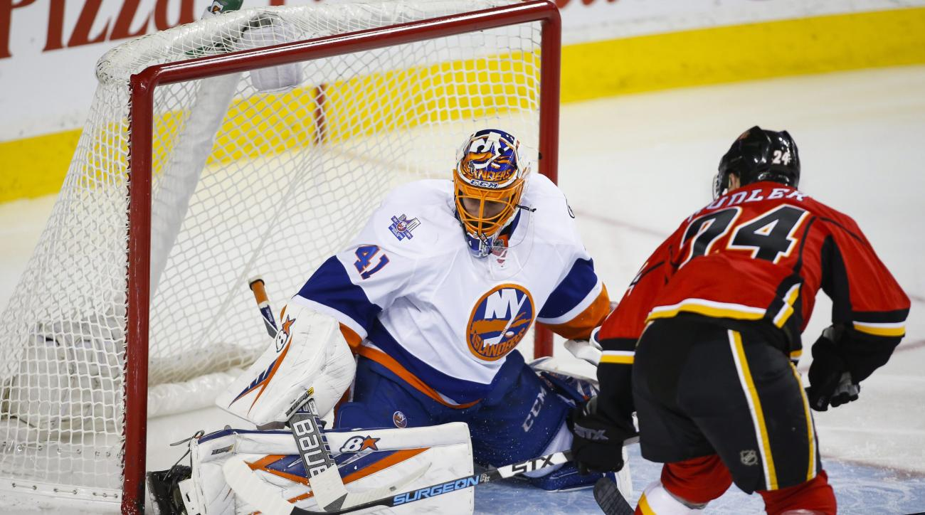 New York Islanders goalie Jaroslav Halak, left, of Slovakia, kicks away a shot from Calgary Flames' Jiri Hudler, from the Czech Republic, during third period NHL hockey action in Calgary, Alberta, Thursday, Feb. 25, 2016. (Jeff McIntosh/The Canadian Press