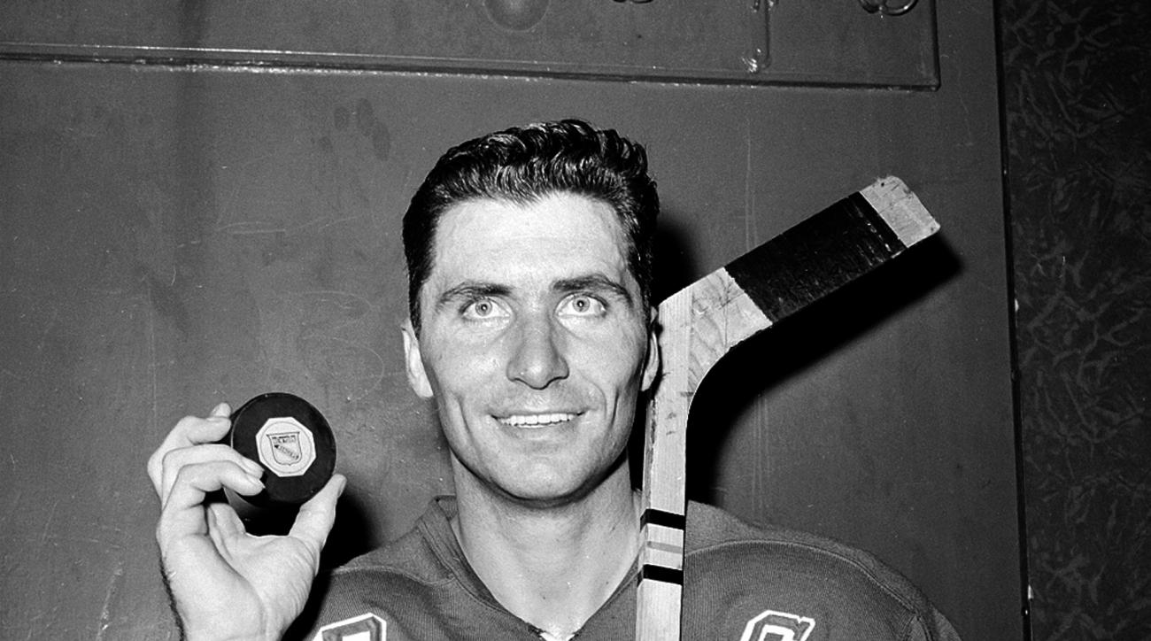 FILE - In this Nov. 12, 1961, file photo, New York Rangers forward Andy Bathgate poses in the locker room at New York's Madison Square Garden,  holding the puck that accounted for the 200th goal of his career, which he scored against the Chicago Blackhawk