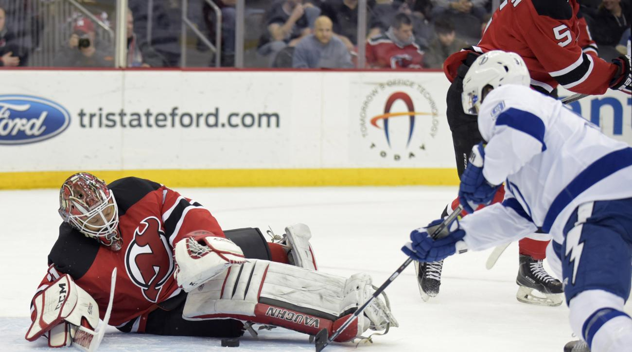 New Jersey Devils goaltender Cory Schneider makes a save as Tampa Bay Lightning's Tyler Johnson, right, attempts to poke the puck into the goal during the first period of an NHL hockey game Friday, Feb. 26, 2016, in Newark, N.J. (AP Photo/Bill Kostroun)