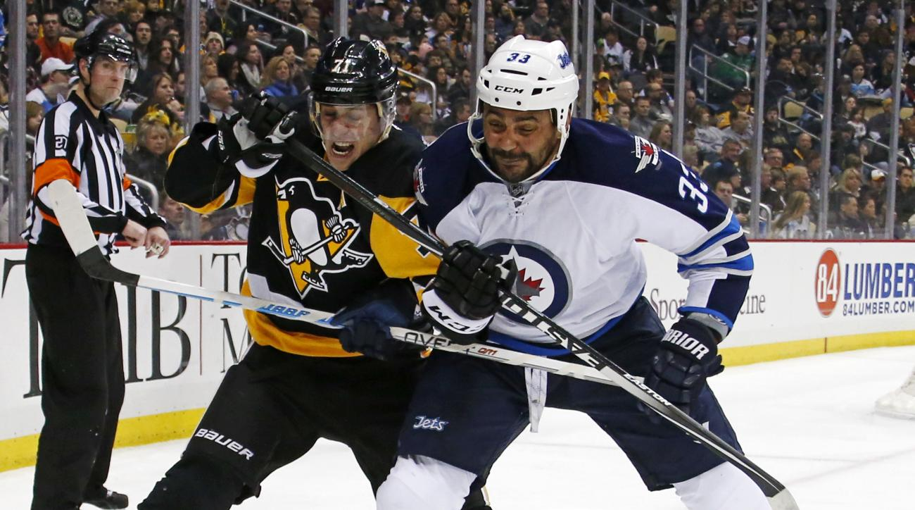 Pittsburgh Penguins' Evgeni Malkin (71) and Winnipeg Jets' Dustin Byfuglien (33) battle in the corner during the second period of an NHL hockey game in Pittsburgh, Saturday, Feb. 27, 2016. (AP Photo/Gene J. Puskar)