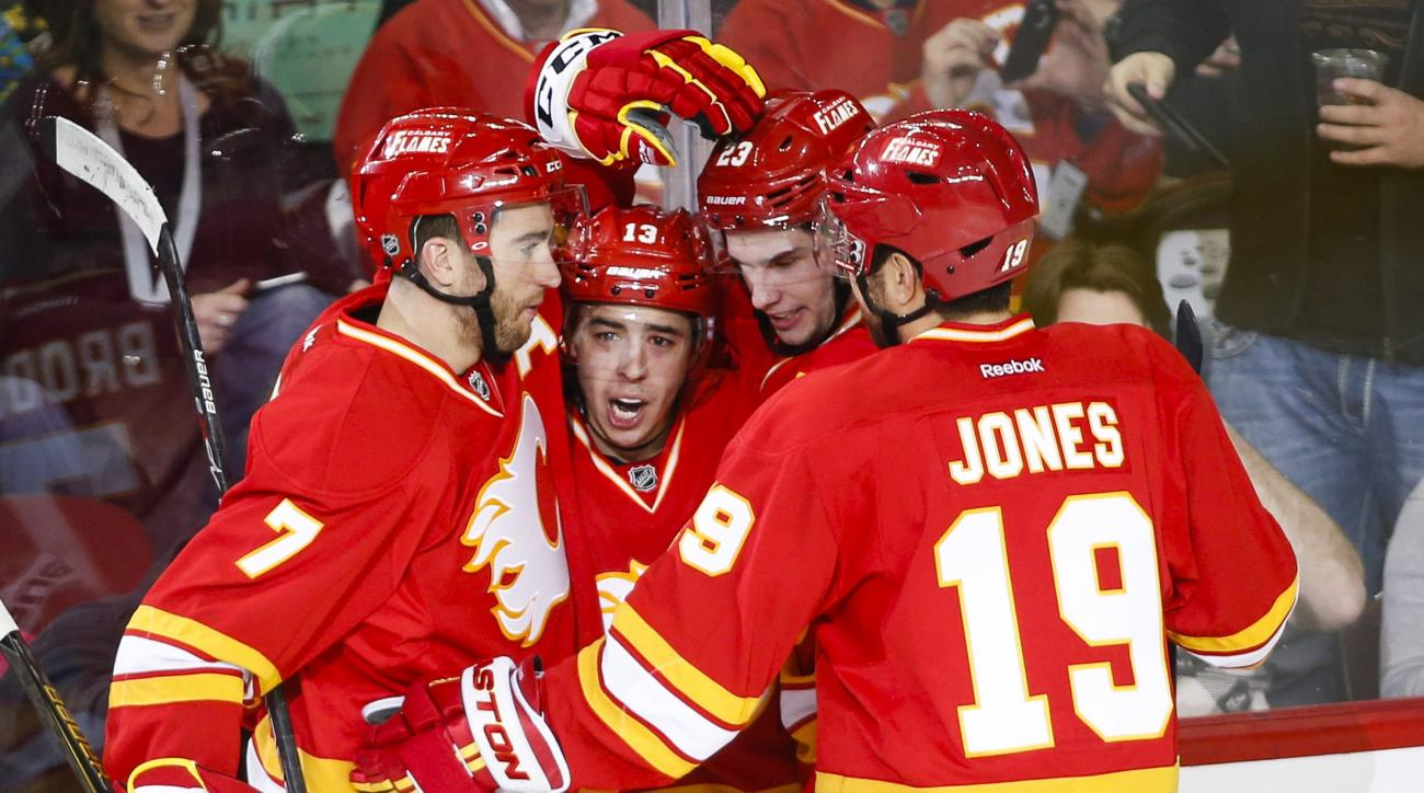 Calgary Flames' Johnny Gaudreau, second from left, celebrates his goal with teammates T. J. Brodie, (7) Sean Monahan and David Jones (19) during the second period of an NHL hockey game against the Ottawa Senators on Saturday, Feb. 27, 2016, in Calgary, Al