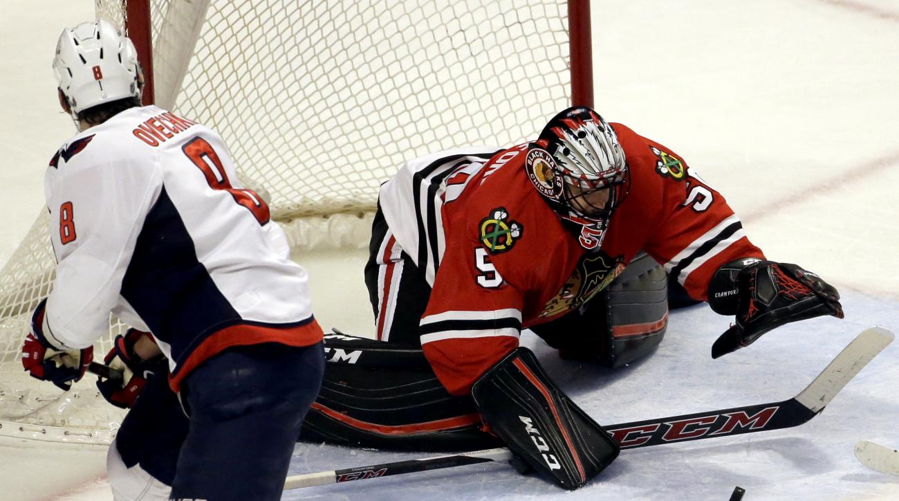 Chicago Blackhawks goalie Corey Crawford, right, saves a shot by Washington Capitals left wing Alex Ovechkin during the second period of an NHL hockey game Sunday,Feb. 28, 2016, in Chicago. (AP Photo/Nam Y. Huh)