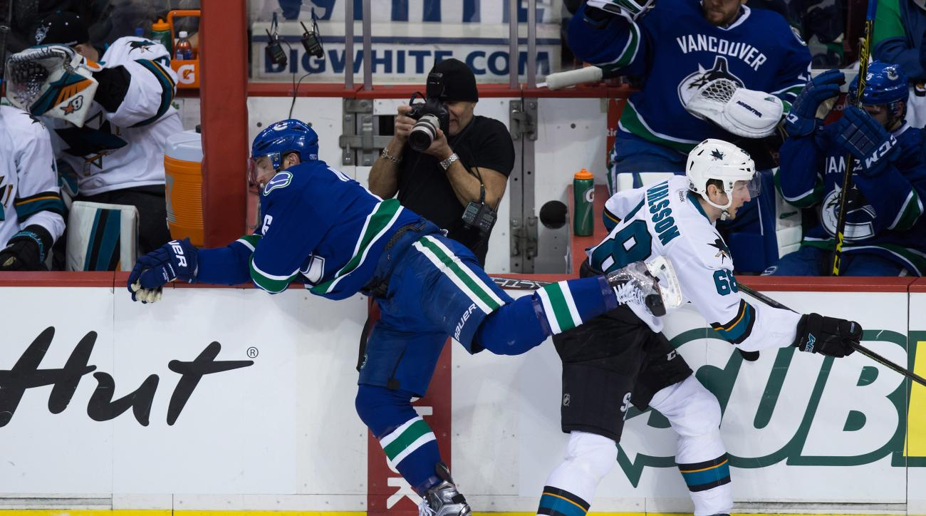 Vancouver Canucks' Yannick Weber, left, of Switzerland, and San Jose Sharks' Melker Karlsson, of Sweden, collide during second period NHL hockey action in Vancouver on Sunday, Feb. 28, 2016. (Darryl Dyck/The Canadian Press via AP) MANDATORY CREDIT