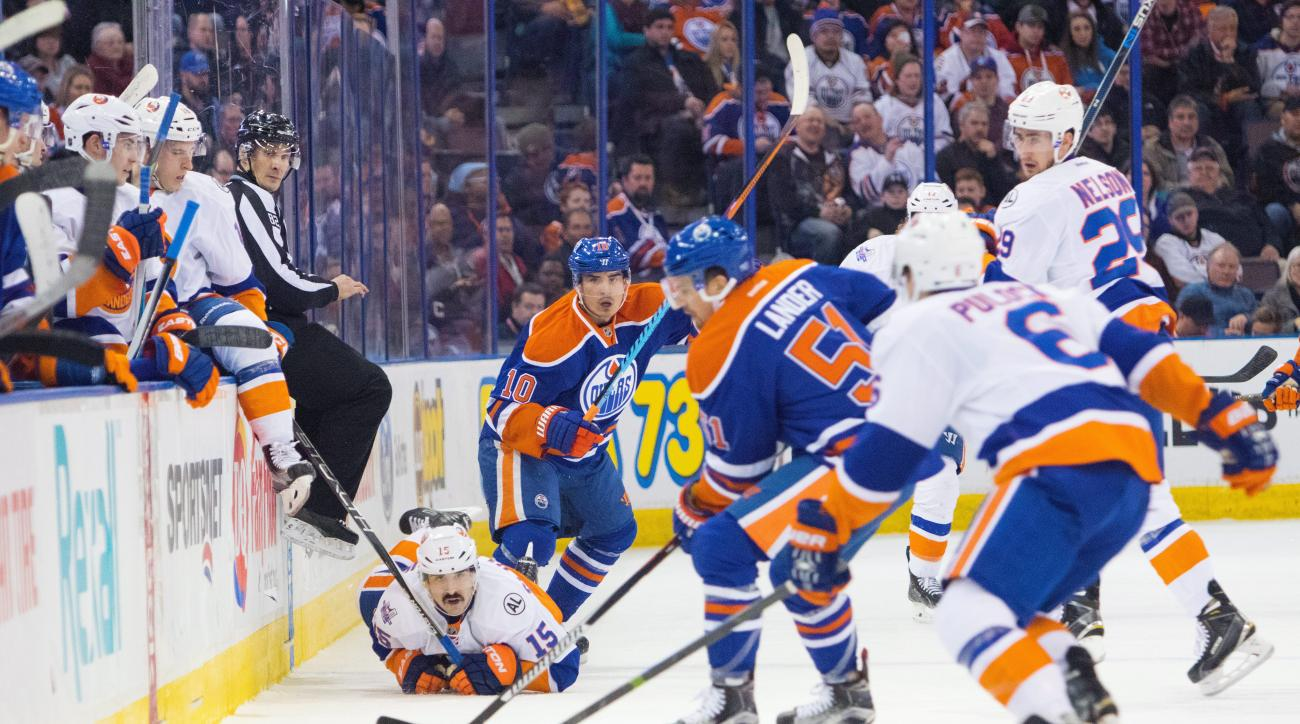New York Islanders' Cal Clutterbuck (15) and Edmonton Oilers' Nail Yakupov (10) watch the puck as Anton Lander (51) scoops it up and Ryan Pulock (6) and Brock Nelson (29) look on during second period NHL hockey action in Edmonton on Sunday, Feb. 28, 2016.