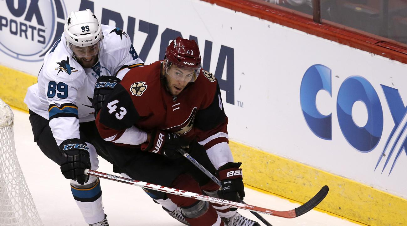 FILE - In this Oct. 2, 2015, file photo, Arizona Coyotes left wing Matthias Plachta (43) shields San Jose Sharks left wing Barclay Goodrow in the third period during a preseason NHL hockey game, in Glendale, Ariz. The Arizona Coyotes and Pittsburgh Pengui