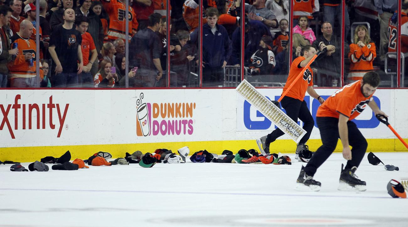 "Members of the ice crew pick up hats tossed on to the ice by Philadelphia Flyers fans celebrating Brayden Schenn's third goal, a ""hat trick"", during the second period of an NHL hockey game against the Calgary Flames on Monday, Feb. 29, 2016 in Philadelphi"