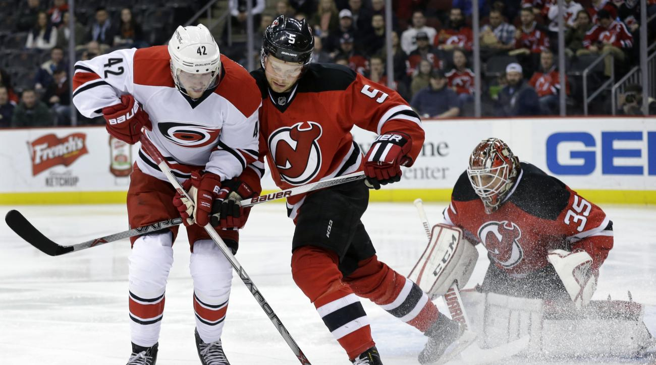 As New Jersey Devils goalie Cory Schneider (35) looks on, teammate Devils defenseman Adam Larsson (5), of Sweden shoves Carolina Hurricanes left wing Joakim Nordstrom (42), of Sweden during the first period of an NHL hockey game Tuesday, March 1, 2016, in
