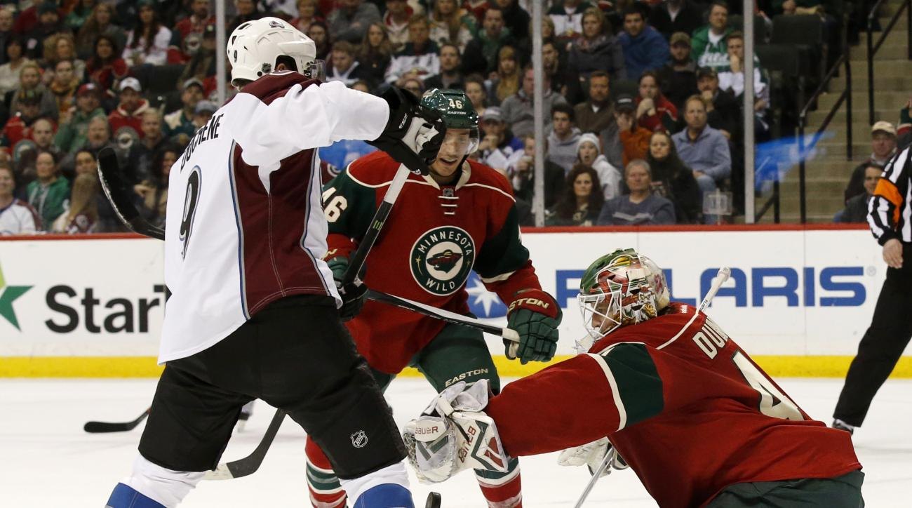 Minnesota Wild goalie Devan Dubnyk (40) stops a shot by Colorado Avalanche center Matt Duchene (9) in front of Wild defenseman Jared Spurgeon, center, during the second period of an NHL hockey game in St. Paul, Minn., Tuesday, March 1, 2016.  (AP Photo/An