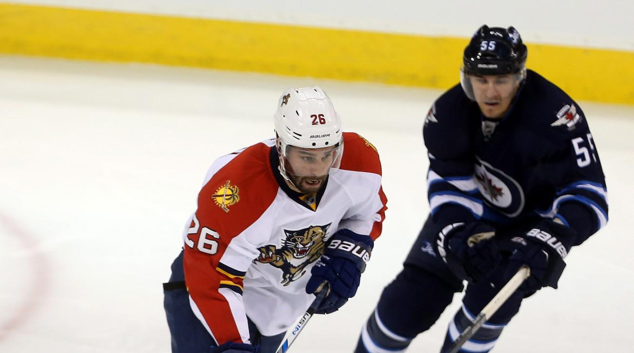 Florida Panthers' Teddy Purcell (26) carries the puck past Winnipeg Jets' Mark Scheifele (55) during the third period of an NHL hockey game Tuesday, March 1, 2016, in Winnipeg, Manitoba. (Trevor Hagan/The Canadian Press via AP)