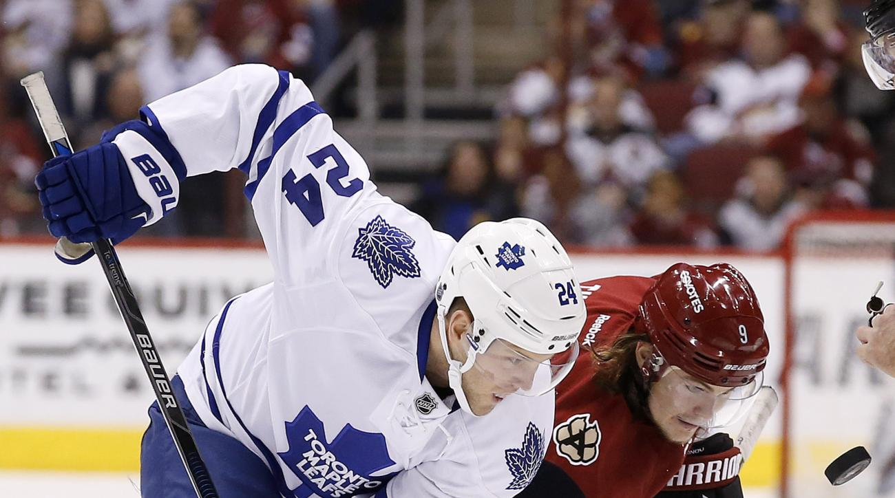 FILE - In this Dec. 22, 2015, file photo, Toronto Maple Leafs' Peter Holland (24) and Arizona Coyotes' Viktor Tikhonov (9), of Russia, watch the puck drop during a face off during the first period of an NHL hockey game, in Glendale, Ariz. Analytics have s