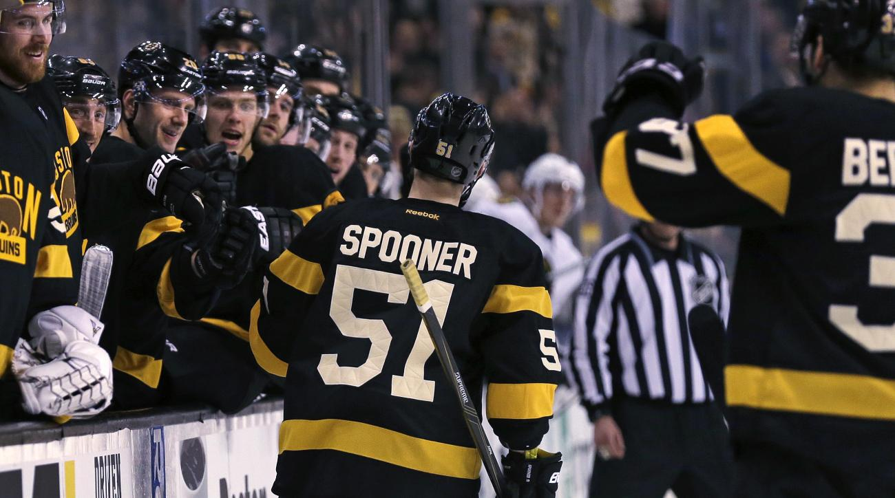 Boston Bruins center Ryan Spooner (51) is congratulated by teammates after his goal against Chicago Blackhawks goalie Scott Darling during the second period of an NHL hockey game in Boston, Thursday, March 3, 2016. (AP Photo/Charles Krupa)