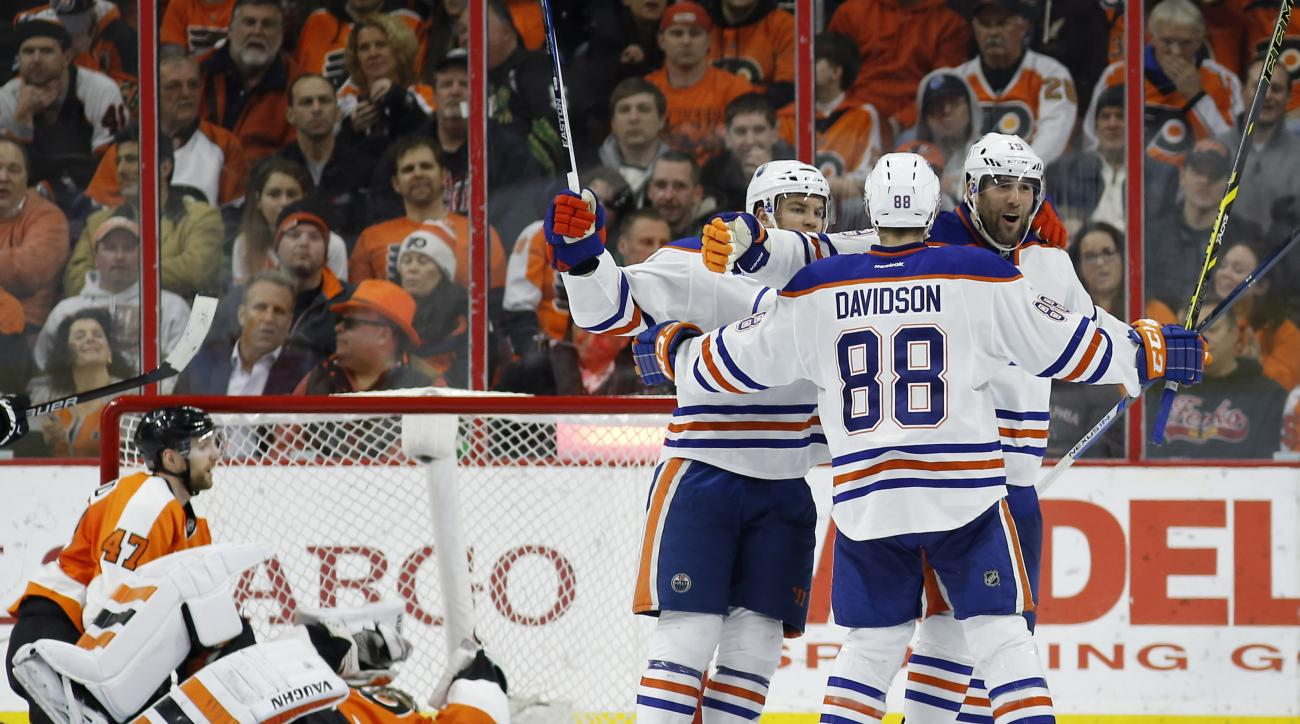 From right to left, Edmonton Oilers' Patrick Maroon, Brandon Davidson and Taylor Hall celebrate after Maroon's goal against Philadelphia Flyers' Michal Neuvirth and Andrew MacDonald during the second period of an NHL hockey game, Thursday, March 3, 2016,