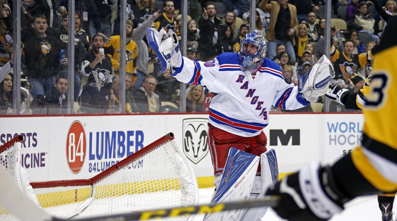 New York Rangers goalie Henrik Lundqvist (30) gestures to an official after pushing over the goal cage to cause a stoppage of play after being shaken up in a collision with teammate Ryan McDonagh during the second period an NHL hockey game against the Pit