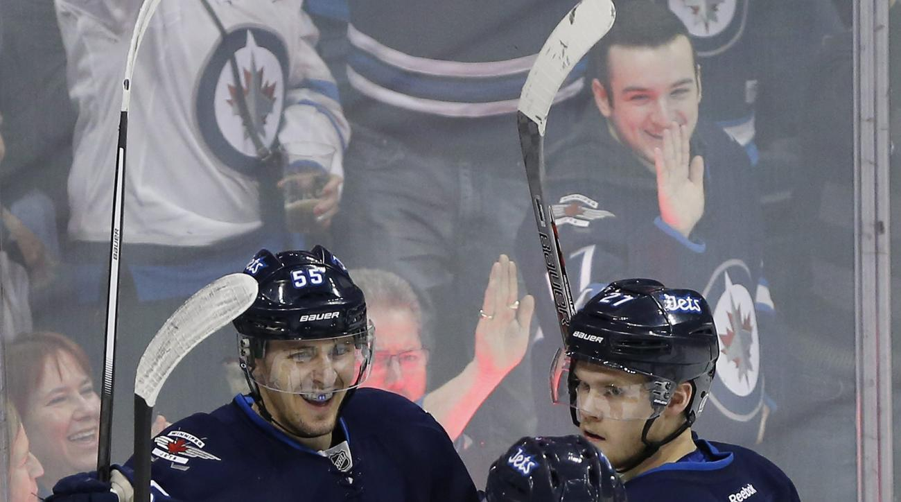 Winnipeg Jets' Nikolaj Ehlers (27), Mathieu Perreault (85) and Mark Scheifele (55) celebrate Scheifele's goal against the New York Islanders during first-period NHL hockey game action in Winnipeg, Manitoba, Thursday, March 3, 2016. (John Woods/The Canadia