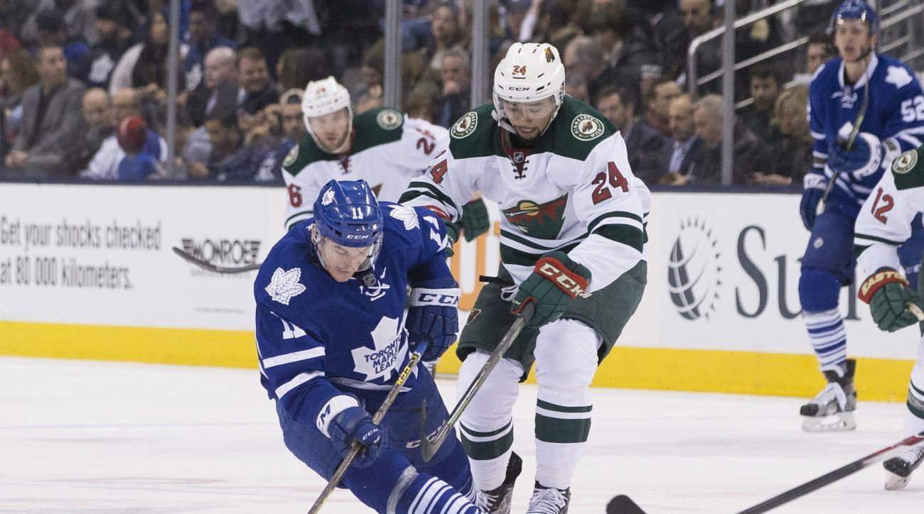 Toronto Maple Leafs' Zach Hyman (11) battles for the puck with Minnesota Wild's Matt Dumba (24) during second-period NHL hockey game action in Toronto, Thursday, March 3, 2016. (Chris Young/The Canadian Press via AP) MANDATORY CREDIT