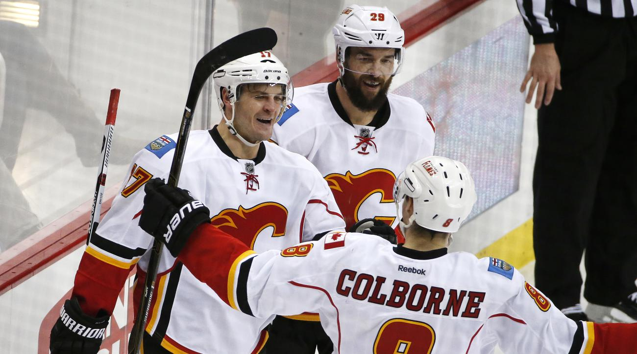 Calgary Flames' Lance Bouma (17) celebrates his goal with teammates Deryk Engelland (29) and Joe Colborne (8) during the third period of an NHL hockey game against the Pittsburgh Penguins in Pittsburgh, Saturday, March 5, 2016. The Flames won 4-2. (AP Pho