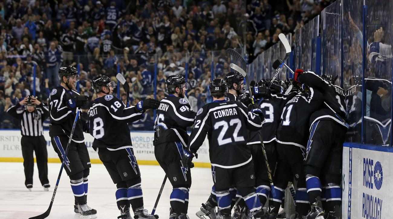 Tampa Bay Lightning players celebrate their overtime win against the Carolina Hurricanes in an NHL hockey game Saturday, March 5, 2016, in Tampa, Fla. The Lightning won 4-3. (AP Photo/Mike Carlson)