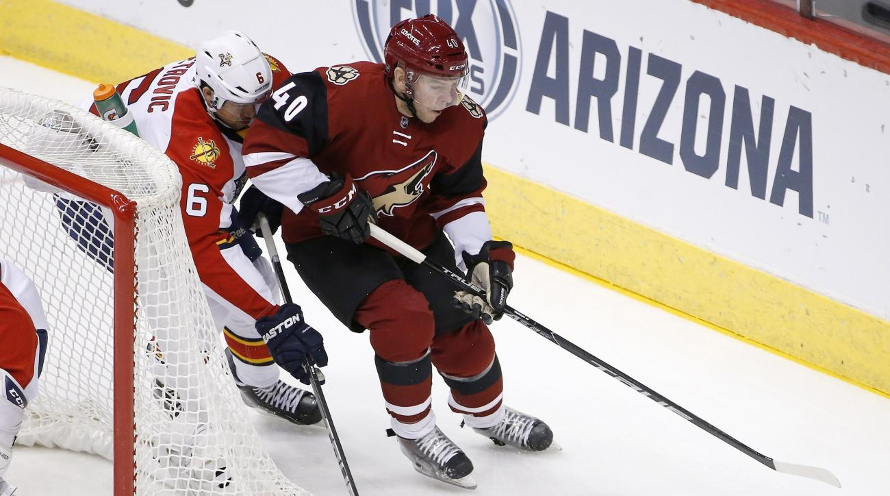 Arizona Coyotes' Alex Tanguay (40) tries to keep the puck away from Florida Panthers' Alex Petrovic (6) during the first period of an NHL hockey game Saturday, March 5, 2016, in Glendale, Ariz. (AP Photo/Ross D. Franklin)