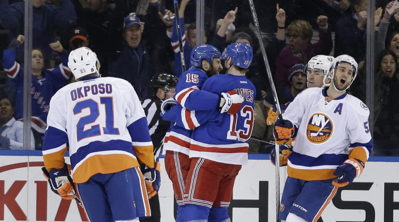 New York Rangers' Tanner Glass, second from left, celebrates his goal with Kevin Hayes, third from left, while New York Islanders' Frans Nielsen, right, reacts, during the first period of the NHL hockey game, Sunday, March 6, 2016, in New York. (AP Photo/