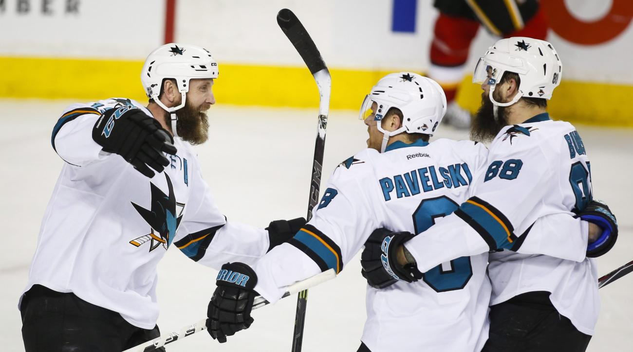San Jose Sharks' Joe Pavelski, centre, celebrtes his game-winning goal with teammates Joe Thornton, left, and Brent Burns during overtime NHL hockey action against the Calgary Flames in Calgary, Alberta, Monday, March 7, 2016. (Jeff McIntosh/The Canadian
