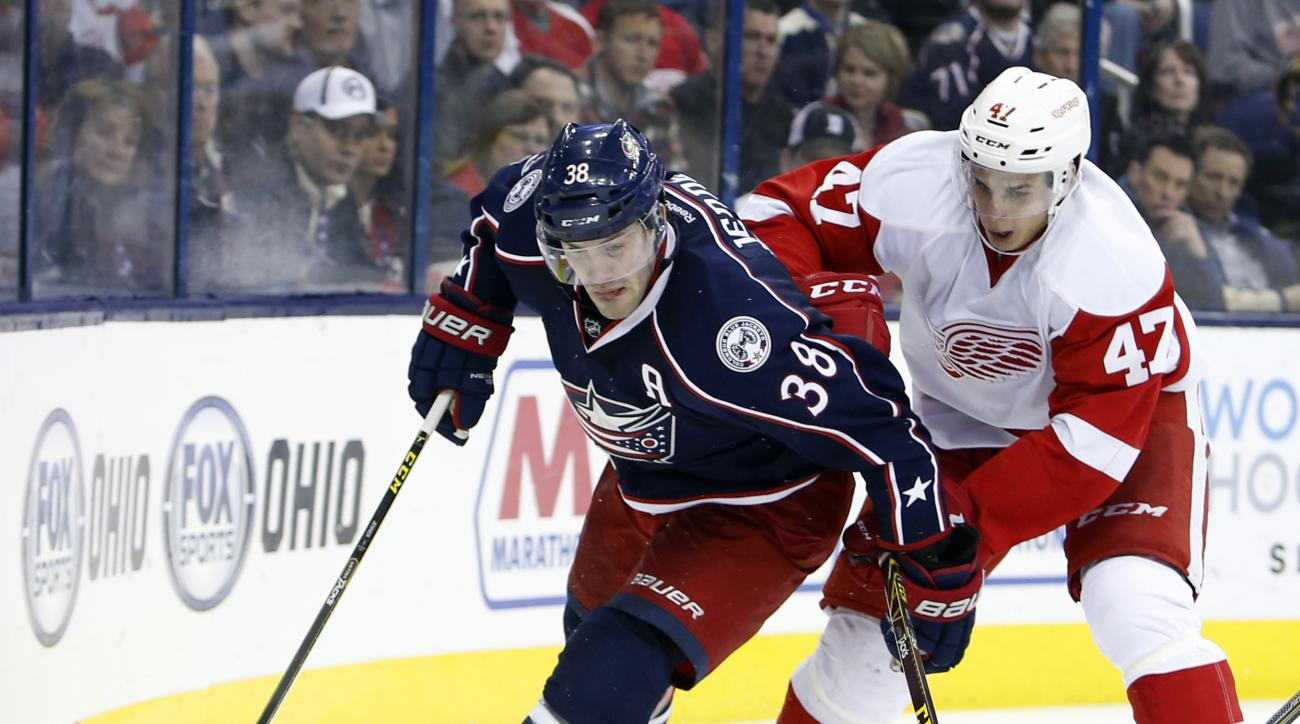 Columbus Blue Jackets' Boone Jenner, left, passes the puck past Detroit Red Wings' Alexey Marchenko, of Russia, during the second period of an NHL hockey game, Tuesday, March 8, 2016, in Columbus, Ohio. (AP Photo/Jay LaPrete)
