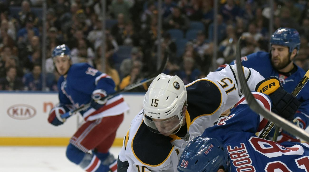 Buffalo Sabres center Jack Eichel (15) battles for the puck with New York Rangers center Dominic Moore (28) during the second period of an NHL hockey game, Tuesday, March 8, 2016, in Buffalo, N.Y. (AP Photo/Gary Wiepert)